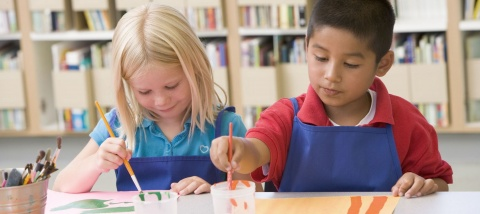Two children working on arts and crafts in a classroom.